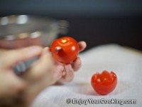 Cut top part of tomato with sharp knife, then cut once more at about 60 degrees